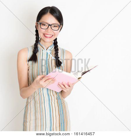 Portrait of young Asian woman in traditional qipao dress smiling and reading book, standing on plain background.