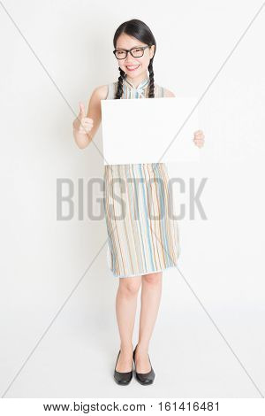 Portrait of young Asian girl in traditional qipao dress hand holding white blank paper card and giving thumb up, celebrating Chinese Lunar New Yearl, full body standing on plain background.
