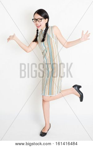 Portrait of excited young Asian girl in traditional qipao dress jumping around, full length standing on plain background.