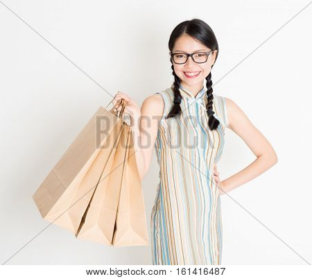 Portrait of young Asian woman in traditional qipao dress shopping, hand holding paper bag, celebrating Chinese Lunar New Year or spring festival, standing on plain background.