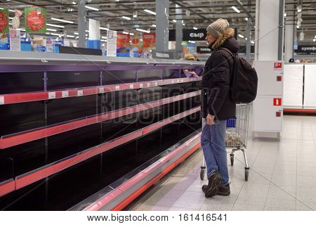 ST. PETERSBURG, RUSSIA - NOVEMBER 29, 2016: Buyer in front of empty shelves in the Finnish hypermarket K-Ruoka. Next day K-Ruoka closes all hypermarkets in Russia selling the business to Lenta
