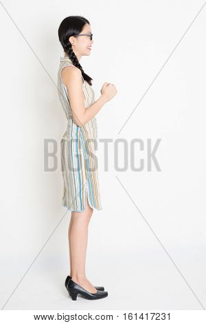 Side view or profile of young Asian girl in traditional qipao dress greeting, celebrating Chinese Lunar New Year, full length standing on plain background.