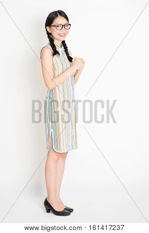 Portrait of young Asian girl in traditional qipao dress greeting, celebrating Chinese Lunar New Year or spring festival, full length standing on plain background.