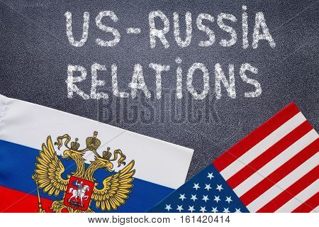 US - Russia relations text written on chalkboard, Flags of USA and Russia. Politics concept