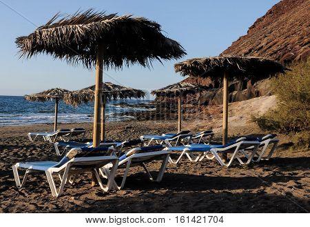 Deckchairs On A Lonely Desert Beach