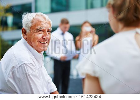 Old businessman talking to business team during negotiations outdoors