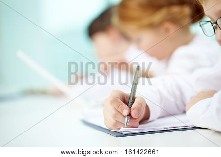 Close-up of child writing in his workbook