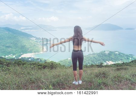 Back view of fitness woman standing on green mountain with her arms outstretched looking at sea landscape expressing happiness and freedom.