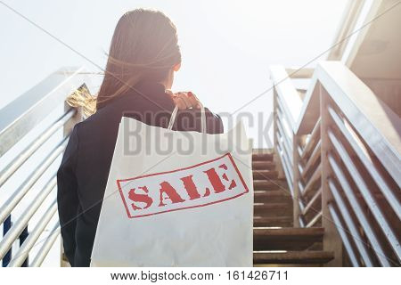 Back view of young woman with shopping bag coming upstairs.