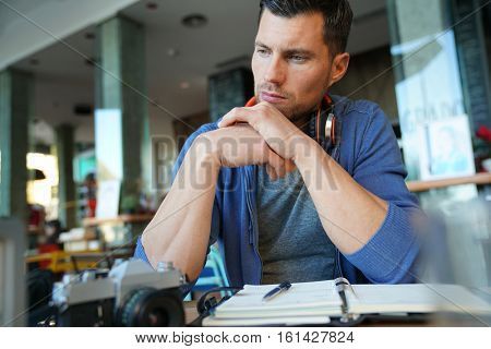 Man sitting in restaurant writing notes on agenda
