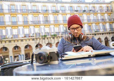Hipster guy relaxing at caf�½ terrace, using smartphone