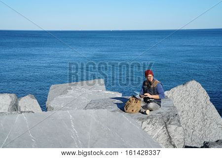 Young reporter connected on tablet by the ocean