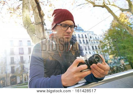 Hipster guy taking pictures in town
