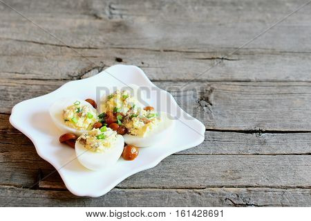 Classic stuffed eggs on a plate isolated on old wooden background with copy space for text. Hard-boiled eggs stuffed with cheese, mushrooms and green onions. Delicious vegetarian snack recipe
