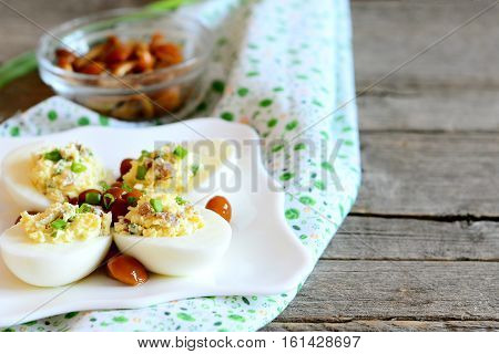 Tasty stuffed eggs on a plate, canned mushrooms in a bowl on old wooden table. Hard-boiled eggs stuffed with cheese, mushrooms and green onions. Easy and beautiful vegetarian snack. Closeup