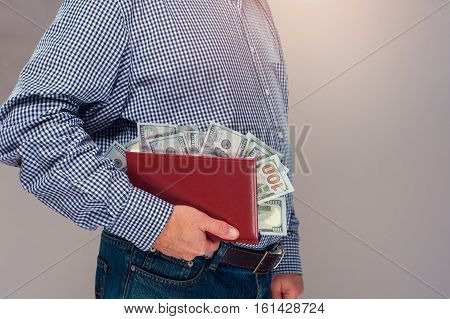 Cropped shot of senior man in casual cloth holding diary with dollar bills. Money stacks on in book.