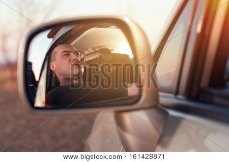 Young drunk man driving a car and drinking beer. Transportation and vehicle safety.