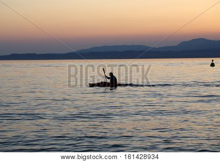 Lonely paddler on the lake during the sunset