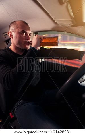 Portrait of young male driver drinking beer in car. Don't drink and drive.