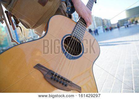 Closeup of folk guitar held by musician walking in the street