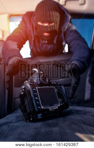 Male thief in black robbery mask stealing photo camera from car
