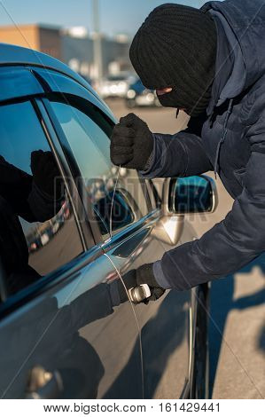 Male thief in black robbery mask breaking into car with screwdriver