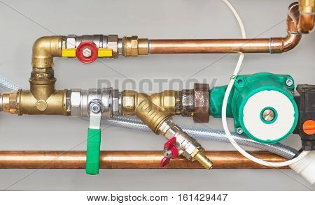 Copper valves pump and pipes on a grey wall
