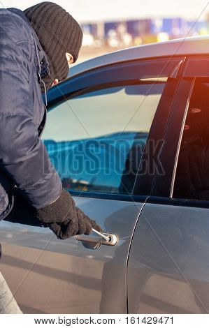 Male thief in black robbery mask opening car door with screwdriver. Auto theft concept.