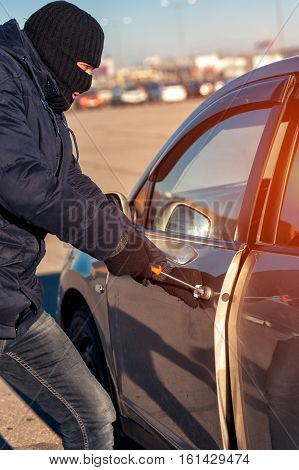 Thief in black robbery mask unlocking car door. Man stealing auto at daylight time.