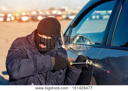 Portrait of male robber in black mask trying to break car with screwdriver. Sunny day light.