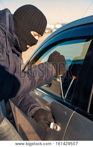 Male Thief Breaking Into Car With Screwdriver
