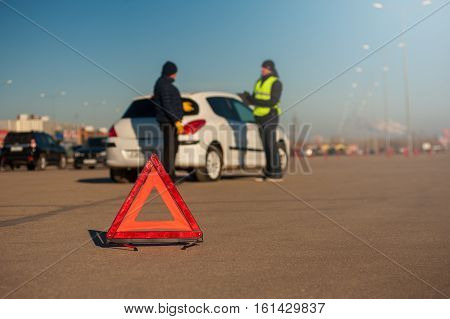 Male driver talking with car assistance technician after breakdown. Repairman with clipboard. Red triangle warning sign foreground