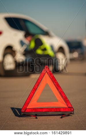 Red emergency warning sign on the background of car assistance technician repairing broken auto.