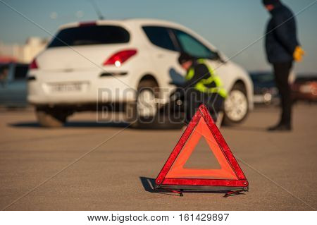 Car repairman changing spare wheel after breakdown. Male driver standing next to auto. Red triangle warning sign foreground.