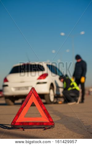 Road assistance technician and driver changing flat tire on parking. Car breakdown outdoors. Red triangle warning sign.
