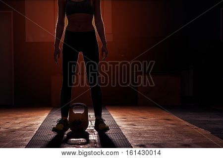 Young sporty girl preparing for kettlebell workout. Muscular woman doing exercises in gym.