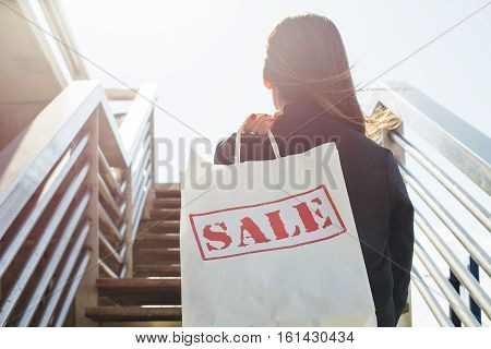 Young female holding white shopping packet and coming upstairs.