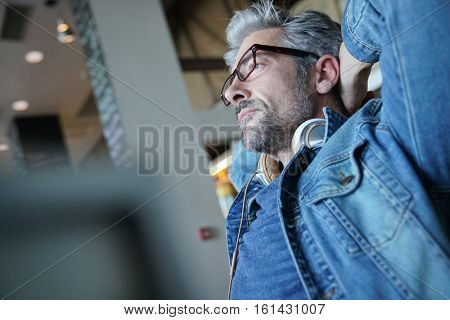 Mature man with blue jeans jacket stretching arms in chair