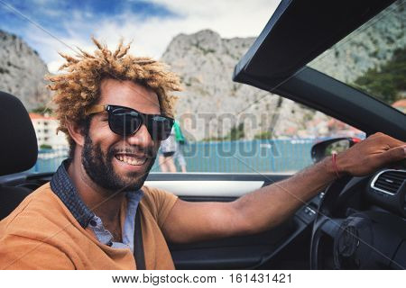 Young happy black man with dread locks wearing sunglasses sitting in the convertible car. Vintage film effect applied.