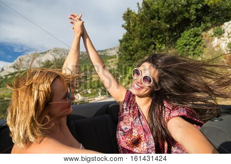 Two girls holding hands and having fun at the back seat of convertible.