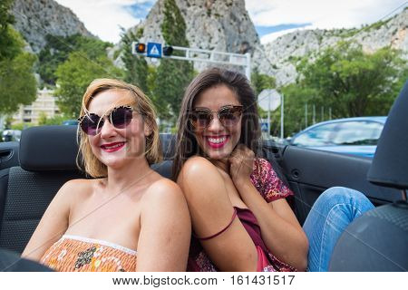 Two girls having fun at the back seat of convertible.
