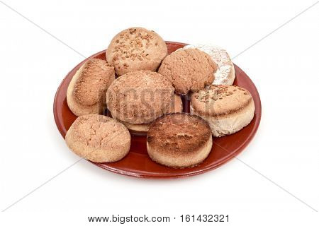 an earthenware plate with different mantecados and polvorones, a typical christmas confection in Spain, on a white background