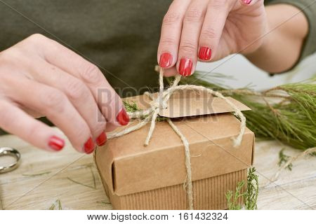 closeup of a young caucasian woman with her fingernails painted red tying a jute string around a brown paperboard gift box, on a rustic wooden surface full of natural twigs and branches