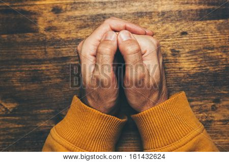 Top view of religious male crossed hands in prayer christian religion practice