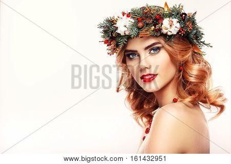 Portrait of beautiful young woman with Christmas wreath. Beautiful New Year and Christmas tree holiday hairstyle and makeup. Beauty girl portrait isolated on a white background. Colorful makeup and hair