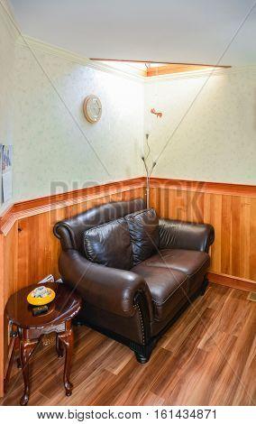 Luxury brown leather loveseat in room corner under the sunroof