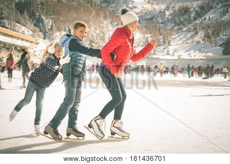 Happy family outdoor ice skating at rink. Mother and children has winter activities. Mom, kids. Medeo stadium. Almaty.
