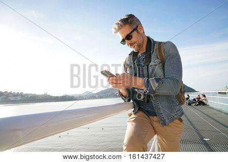 Man standing by the sea using smartphone, winter season