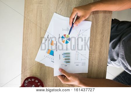 Closeup of male right hand holding pen points on colorful business graph in office top view