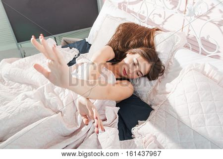 Beautiful girl stretching in bed, free space. Top view on young attractive rested women awaking in bedroom, Morning, rest, relax, awakening concept